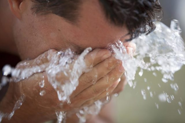 man splashing face with water